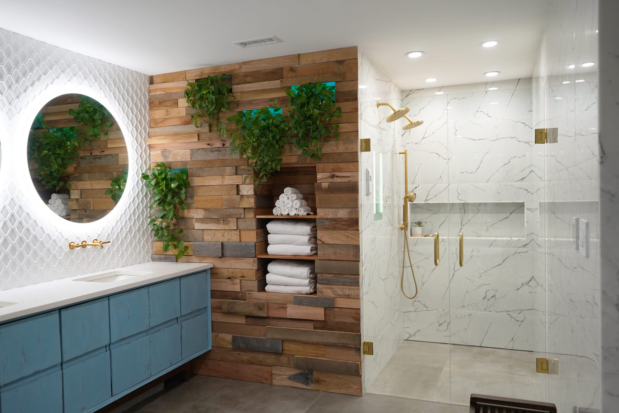 Bathroom Remodel Company in Atlanta with contemporary vanity, marble tile, walk in shower, gold shower, gold faucets, wood wall, white tile, round mirrors.